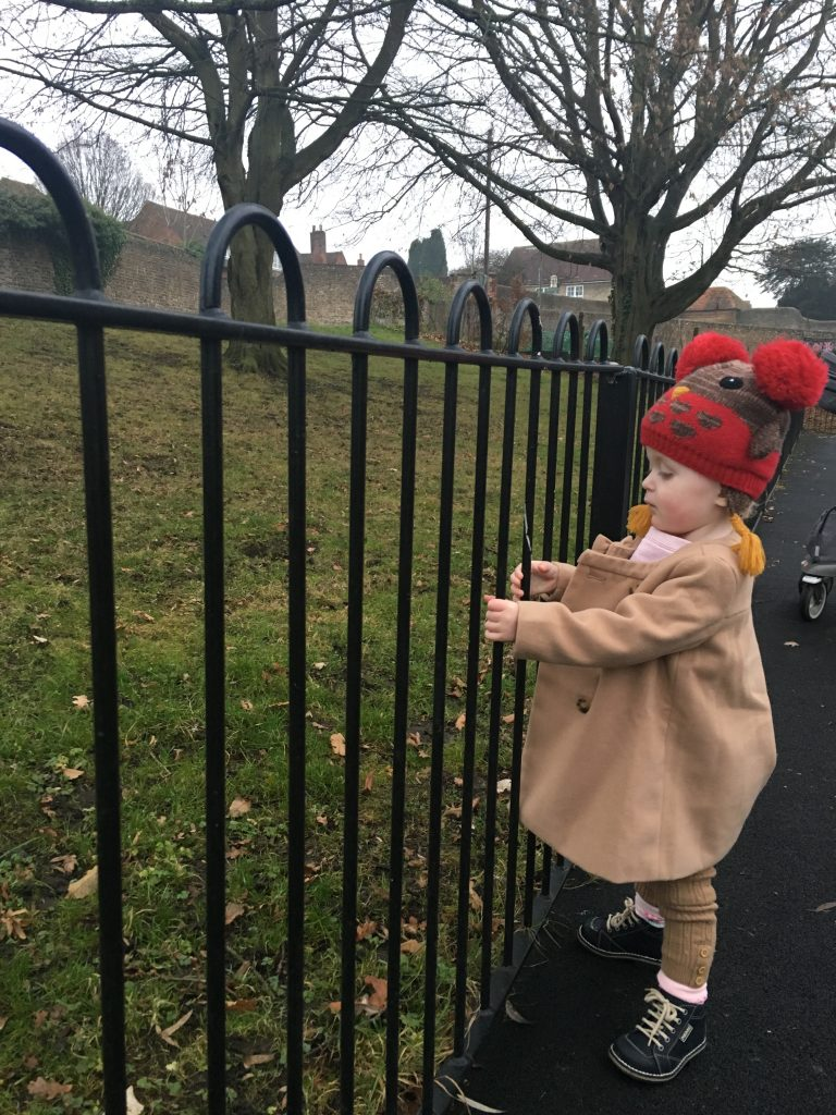 Ariella standing at park fence